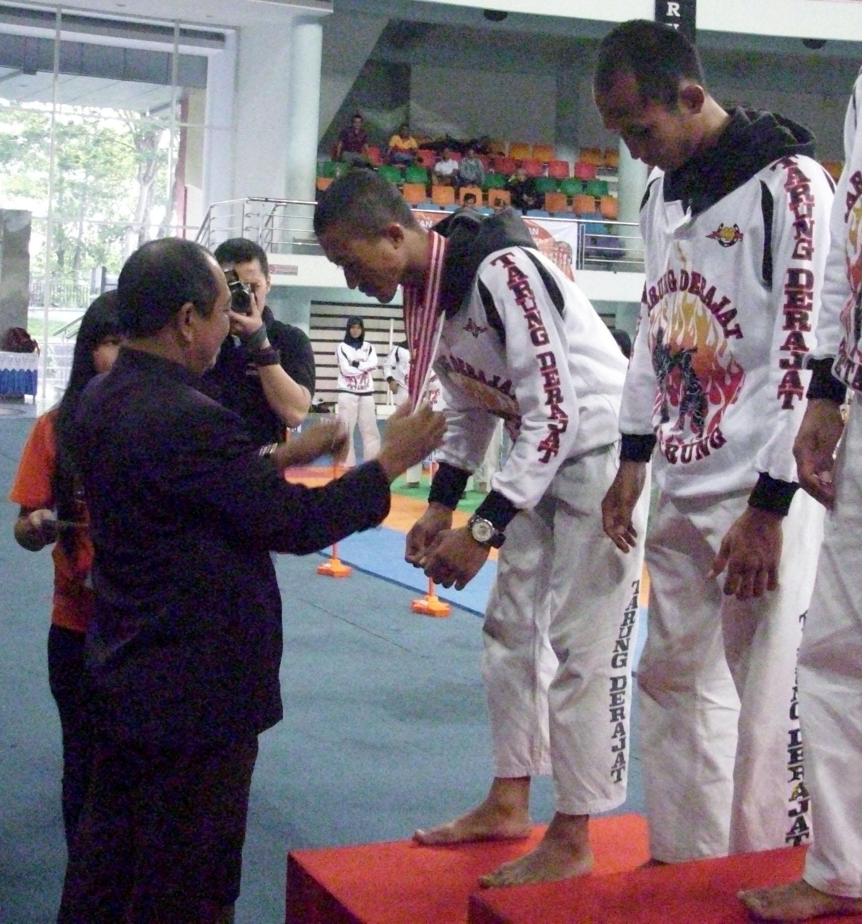 Muhammad Adam (kiri) Ketua KONI daerah Balik Papan mengalungkan medali perunggu kepada Wahyu Sihpikukuh yang menjadi juara tiga pada pertandingan pra-PON di Kalimantan Timur. foto: dok. istimewa
