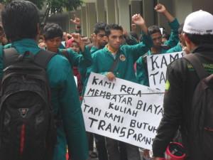 seorang mahasiswa tengah mengikuti aksi demo sembari membawa kertas yang berisi salah satu tuntutan | foto: Desi