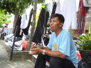 Baharudi, penjual aksesoris Ospek sedang mengunggu pembeli di halaman kampus FKIP UST.