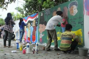 Peserta lomba mural tengah sibuk melukis di tembok pagar pembatas kampus FKIP pada hari Rabu (18/12) siang. | foto: Taofiq