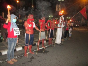 "LMND kota Yogyakarta melakukan aksi ""tutup mulut"" untuk menolak penyelenggaraan KTM WTO di titik nol kilometer Malioboro, Selasa malam (3/12) | foto: dok.istimewa"