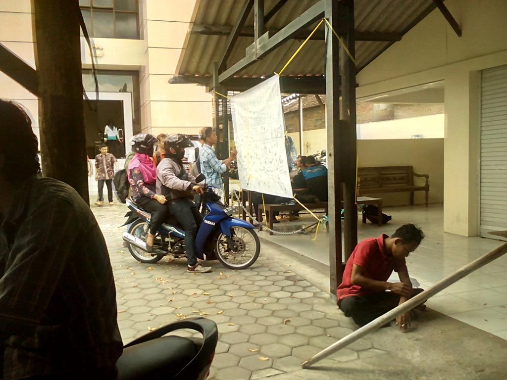 Berhenti dengan berkoncengan motor, dua mahasiswa membubuhkan tanda tangansebagai bentuk  penolakan kenaikan biaya perpanjangan skripsi, pada Kamis (26/02/2015). Foto: Rion, Pendapa.